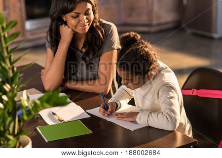 Smiling mother looking at cute little daughter doing homework homework help concept