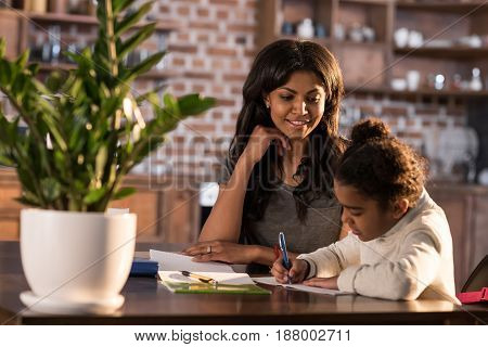 Smiling Mother Looking At Cute Little Daughter Doing Homework, Homework Help Concept