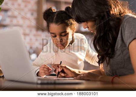 Side View Of Mother Helping Daughter Doing Homework