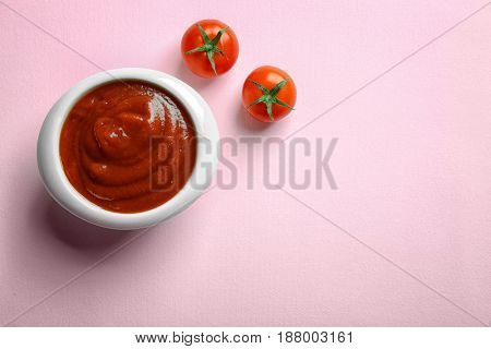 Delicious ketchup in bowl on pink background, top view