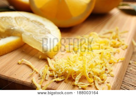 Lemon zest and slices on wooden board, closeup