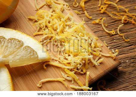Cut lemon and zest on wooden board, closeup