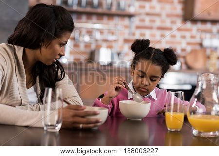 Portrait Of Mother And Daughter Having Breakfast Together At Home