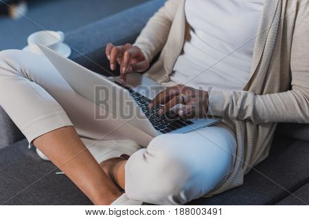 Young Woman Using Laptop While Sitting On Sofa At Home