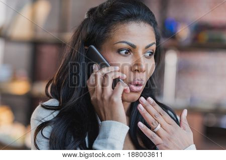 Portrait Of Surprised Young African American Woman Talking On Smartphone At Home