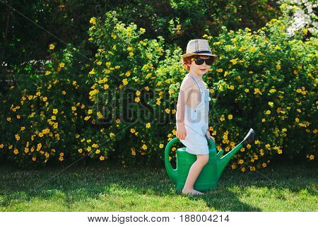 photo of cute little boy with water can in garden