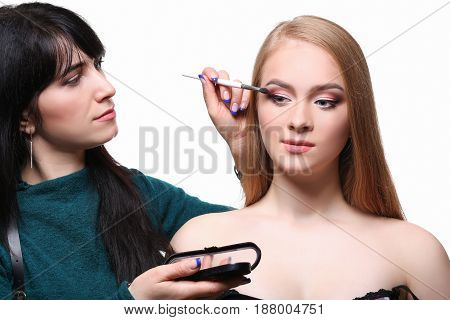 Make-up artist applying makeup for beauty model with eyeshadow palette, isolated on white background