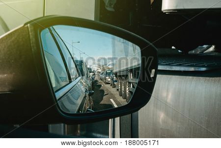 Driver point of view looking in rear view mirror at the traffic jeam behind him on the both lanes transportation delay speed