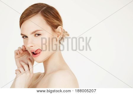 Portrait of young naked beautiful girl with natural make up showing tongue looking at camera over white background. Cosmetology and spa. Copy space.