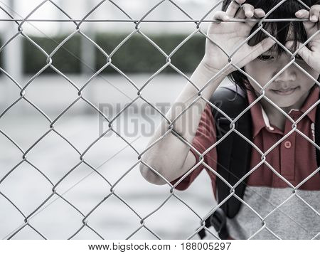 Portrait of handsome sad boy behind fence mesh netting. Emotions concept - sadness sorrow melancholy. Fashion & beauty concept.