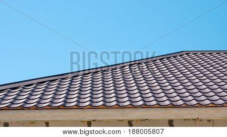 Brown roof of metal roofing on the sky background
