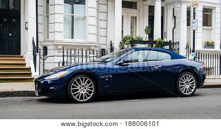LONDON UNITED KINGDOM - MAR 11 2017: Luxury Maseratti GranCabrio blue exclusive cabrio car parked in front typical townhouse city house in London nighwborhood