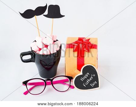 Father's day concept. Happy Father's Day text on black heart wooden gifts glasses note book tea cup with black Mustache and sweet marshmallow in the shape of heart on white background