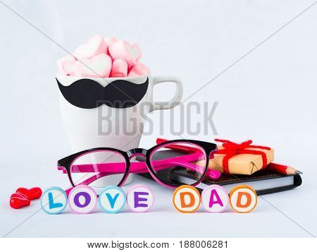 Father's day concept. LOVE DAD alphabet gifts glasses note book tea cup with black Mustache and sweet marshmallow in the shape of heart on white background