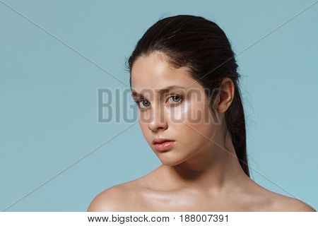 Fashion portrait of young beautiful nude girl with natural make up looking at camera. Copy space.