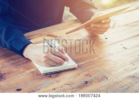 Young Business Man Writing Note Pad And Using Tablet In Coffee Shop Witn Vintage Filter.