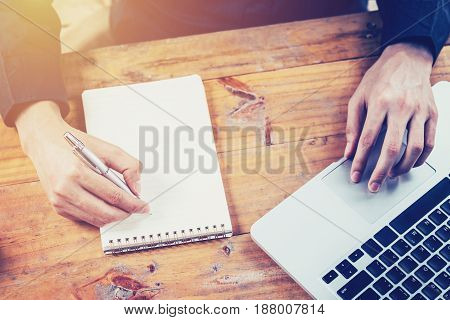 Asia Business Man Hand Using Laptop And Writing Note Pad On Table In Coffee Shop With Vintage Toned