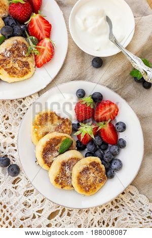 Cottage cheese quark pancakes syrniki with strawberry and blueberry