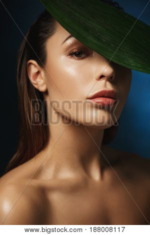 Fashion photography style. Naked woman with trendy make up, wet hair. Geen leaf on forehead.