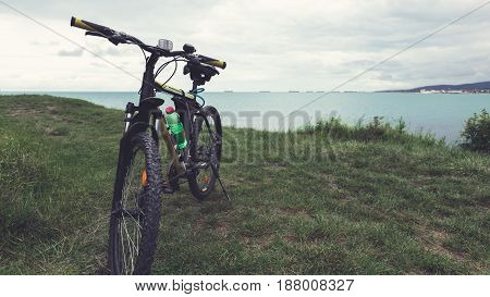 A bicycle stands on a green lawn of the sea coast with a view of the mountain range concept of active recreation and healthy lifestyle