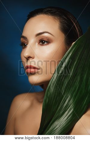 Side view. Closeup portrait. Amazing naked woman with big fresh green leaf on blue background.