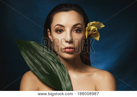 Woman with yellow lily flower behind ear, big green leaf on right shoulder. Looking straight.