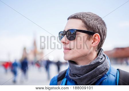 Portrait of a man in sunglasses against the backdrop of city streets