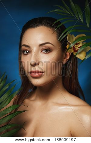 Vertical shot of naked woman with wet slicked back hair, standing behind exotic plants.