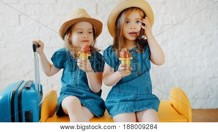 Two little girls eat ice cream at home while waiting for a summer vacation
