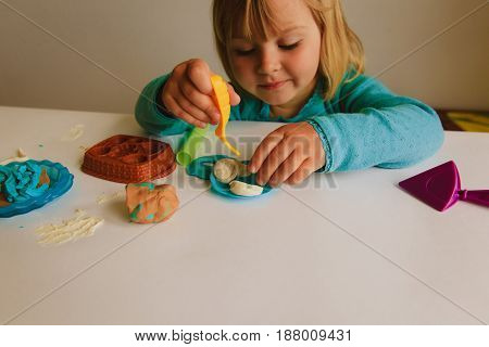 Child playing with clay molding shapes, learning concept
