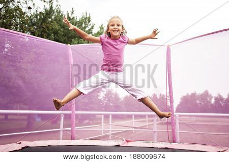 Happy caucasian girl jumping high on a trampoline on a sunny day outdoors.
