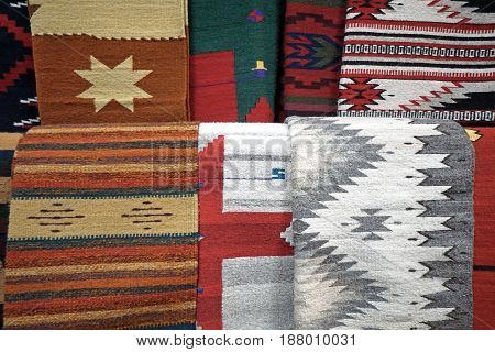 Several woven fabrics with American Southwestern designs hanging together.