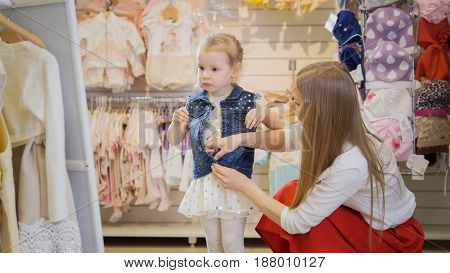Shopping for kids -young mother helping daughter zip up denim jacket in front of a mirror