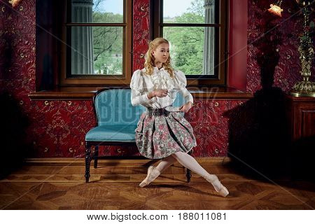 Young blonde ballerina in fashion clothes sitting on sofa and drinking the tea
