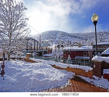 Park City, Utah.  Winter city landscape with houses, trees, a mountain and a bridge covered in snow on a sunny day.