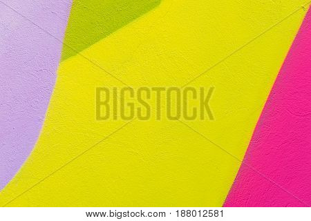 Colorful abstract textured background. Street art, plastered wall facade with green, pink, purple, and yellow paints. Colourful grungy surface with place for copy text