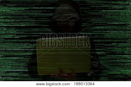 Hacker using laptop stealing data on a code background. Computer security concept