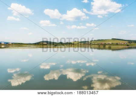 The River, Small Village Behind It And Blue Sky With Clouds, Reflected In The Water.
