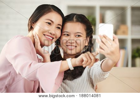Pretty Vietnamese teenage girl taking selfie with her mother
