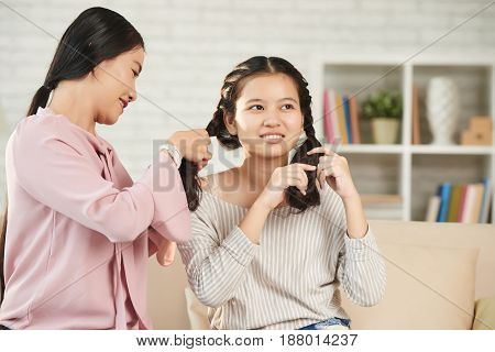 Vietnamese woman braining hair of her teenage daughter