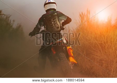 man riding sport enduro motorcycle on dirt track