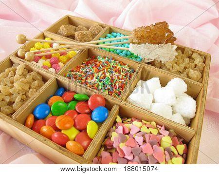 Wooden box with sugar pearls, sugar cubes, sugar herarts and more sweetmeats