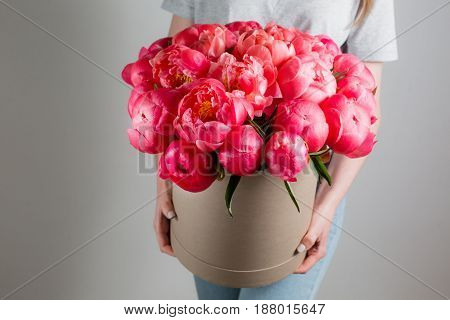 girl holding beautiful mix coral and pink flower bouquet in round box with lid. peonies grade Coral Sharm
