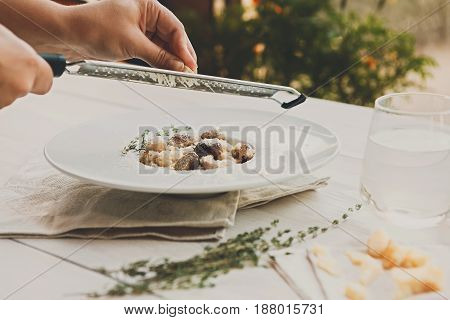 Grating parmesan cheese on wild mushrooms risotto with rosemary. Traditional italian cuisine dish. Restaurant food closeup. Forest fungus with rice. Shallow DOF, selective focus
