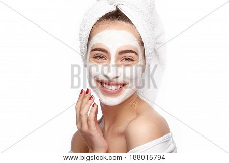Smiling young woman using the white clay mask and looking at camera.