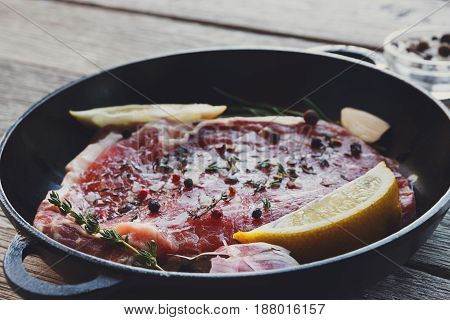 Raw beef steak closeup, selective focus. Fresh juicy meat marinated with herbs and spices, rosemary and lemon slices. Cooking ingredients, butcher's and grocery concept