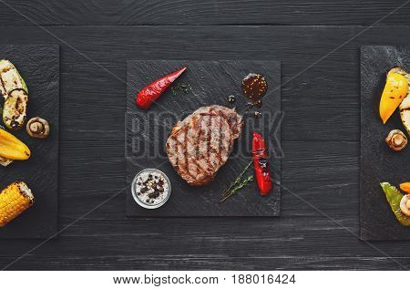 Grilled beef steak and roasted vegetables on dark wooden table background, top view. Juicy meat with rosemary, peppers and cutlery on stone board. restaurant food