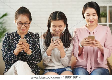 Excited grandmother, daughter and granddaughter playing games on smartphones