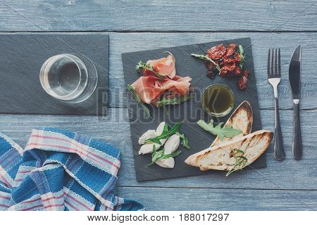 Restaurant platter antipasto with ham prosciutto, bruschetta bread toasts and mozzarella cheese on stone desk on blue wood table top view with glass of wine