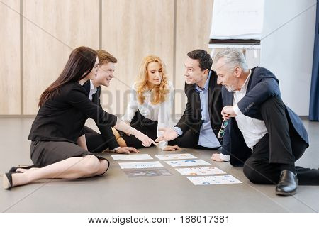 Lets choose this one. Good looking nice attractive woman pointing at the sheet of paper and suggesting to choose it while sitting with her colleagues